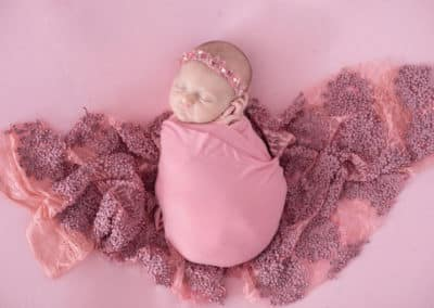 newborn wrapped in blanket with pink background