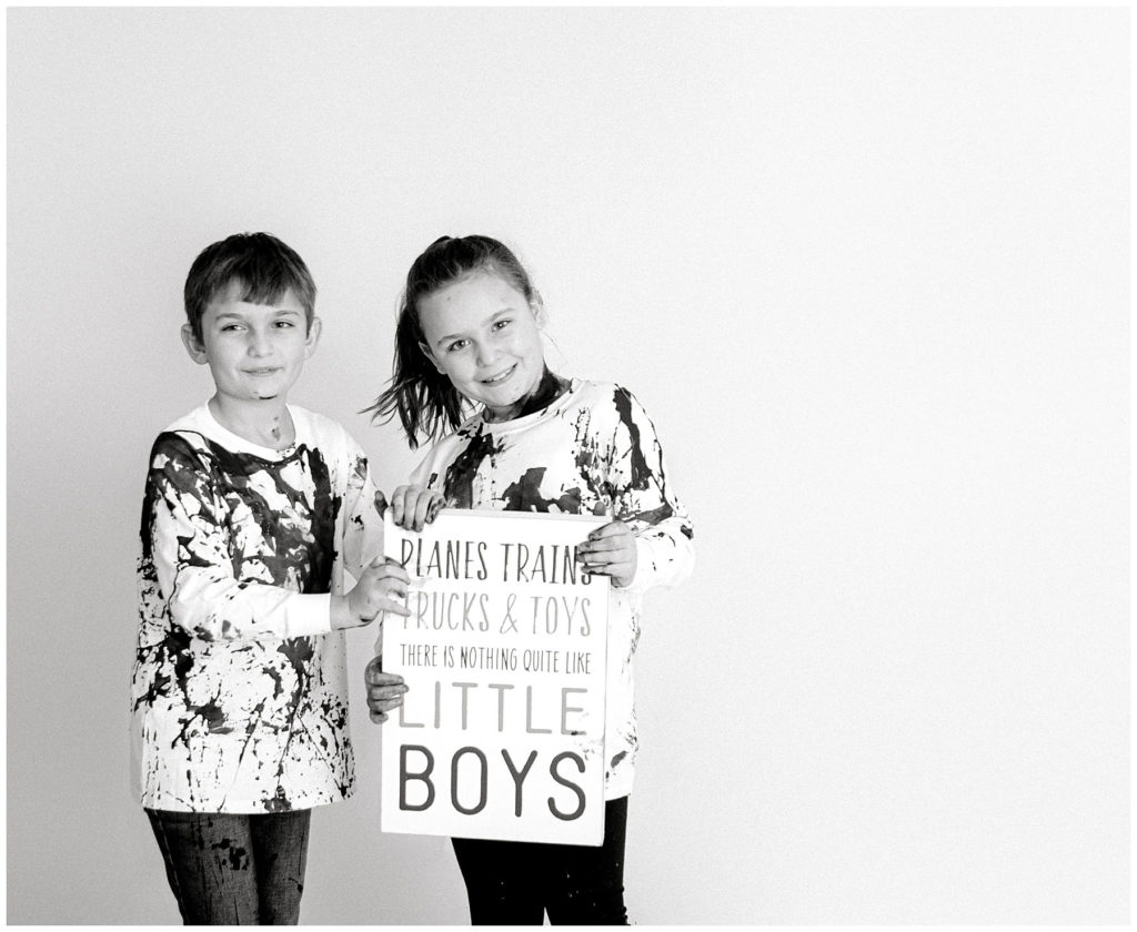 black and white, brother and sister holding sign that baby is a boy