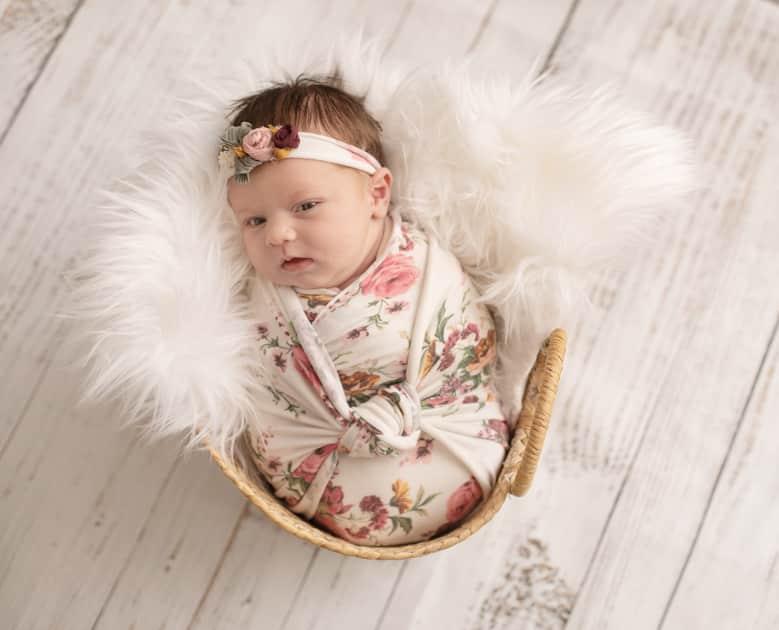 Newborn girl in basket swaddled up