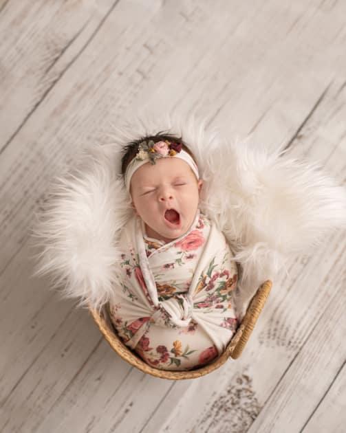 Baby photographer in maine, yawning newborn girl, posed studio newborn