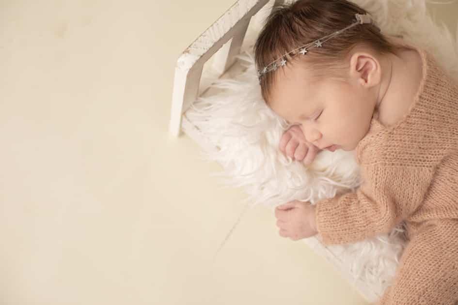 baby photographer in maine, posed newborn in baby crib, augusta maine studio